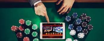 Händer som pekar på platta med casinospel samt spelmarker runtomkring.